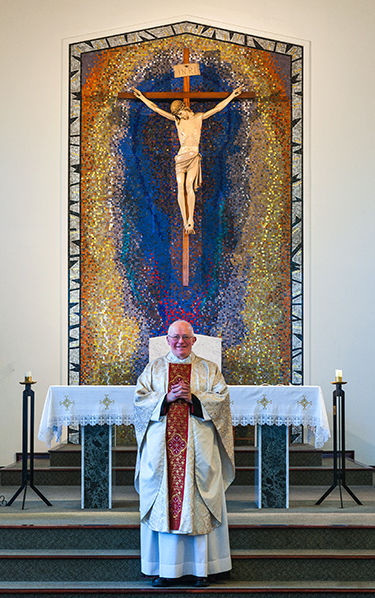 Fr. Michael Loughlin in front of the crucifix and mosaic in St. Andrew's Parish Church, Teesville, in the Diocese of Middlesbrough.